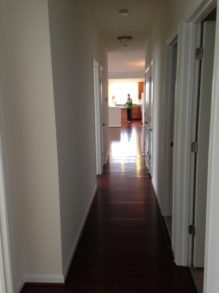hallway of new condo with hardwood flooring
