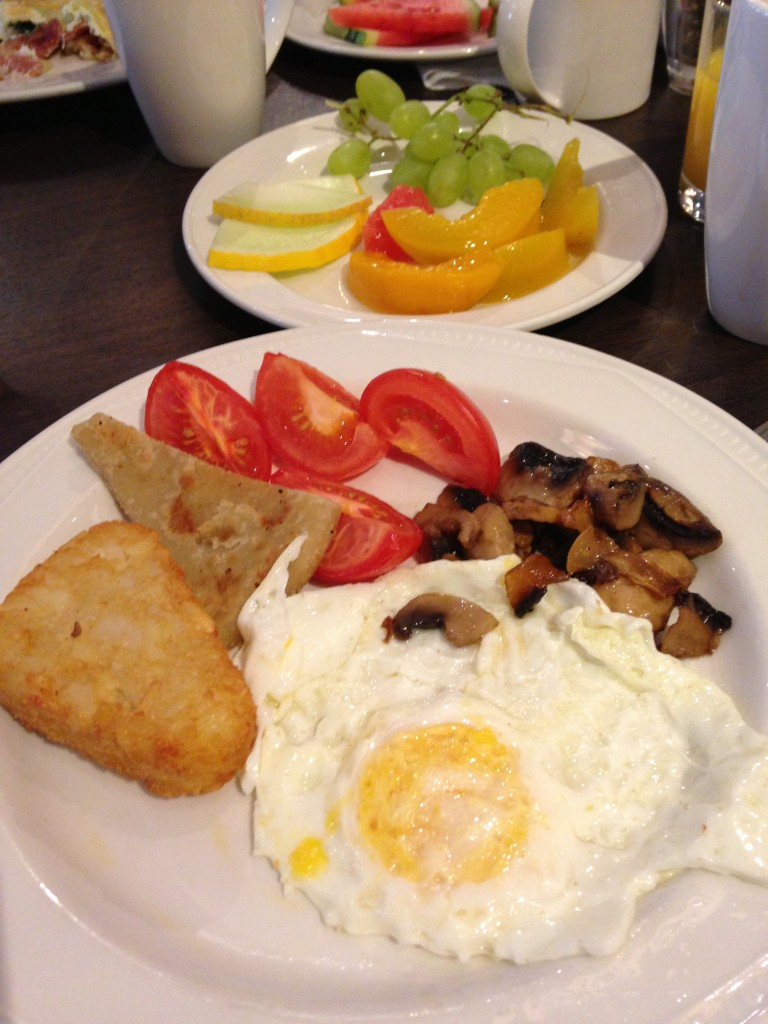breakfast spread at hilton edinburgh with hash brown, tomatoes, mushrooms, fried egg, and fruit