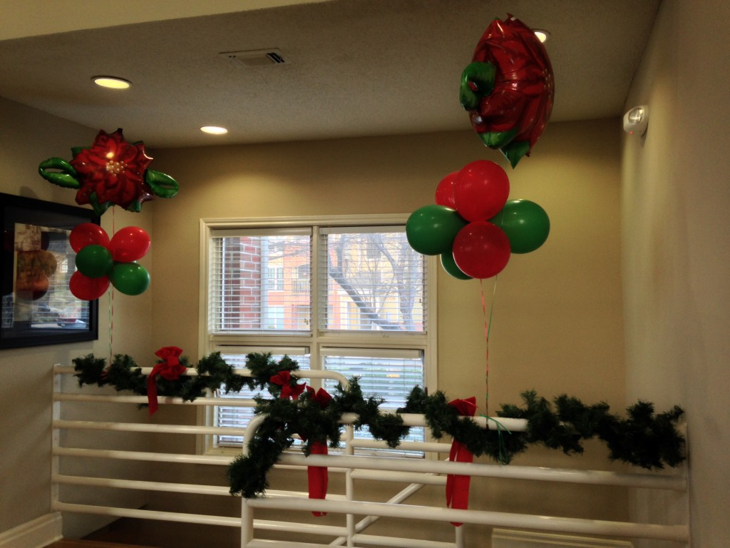 red and green balloons and christmas decorations on railing
