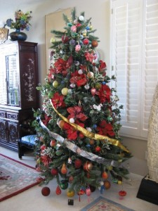 christmas tree in living room decorated with poinsettias and ornaments