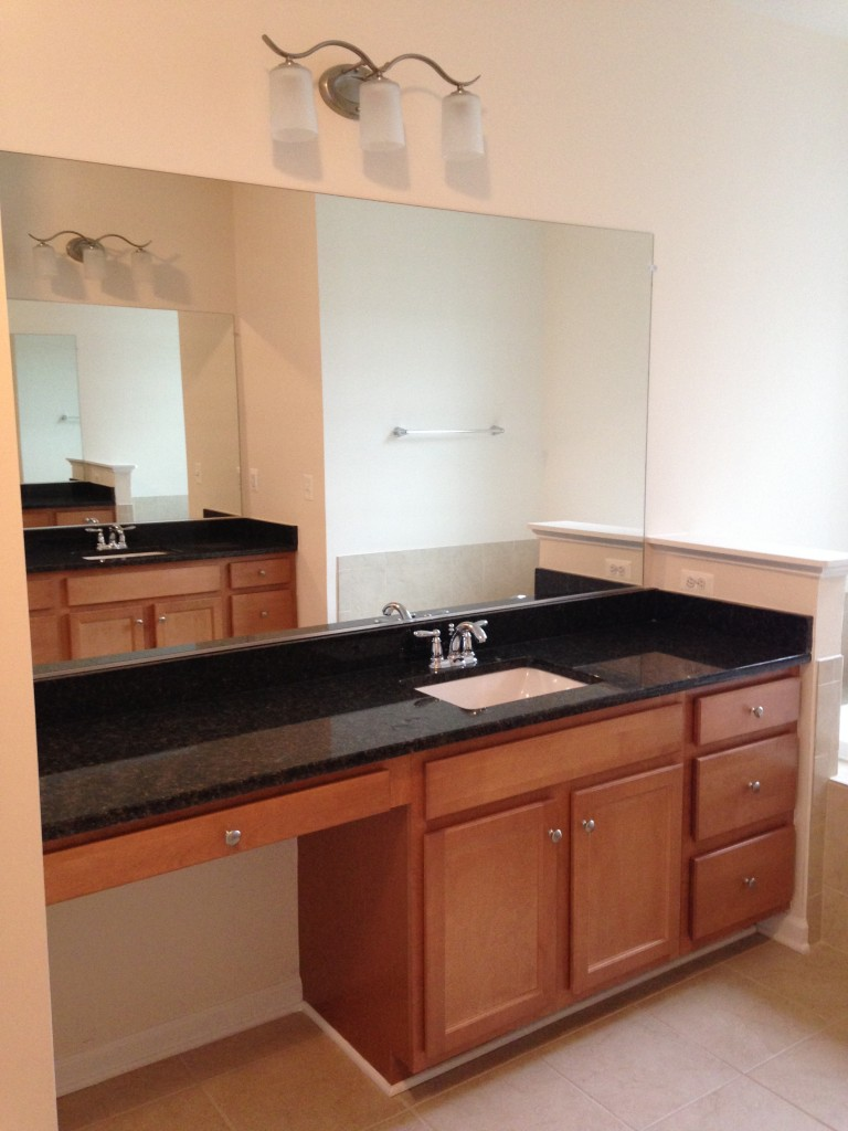 master bathroom sink with vanity area, dark granite countertops, and light wooden drawers