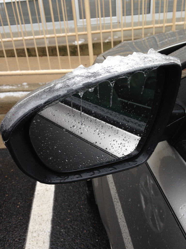 melting icicles on car's mirror