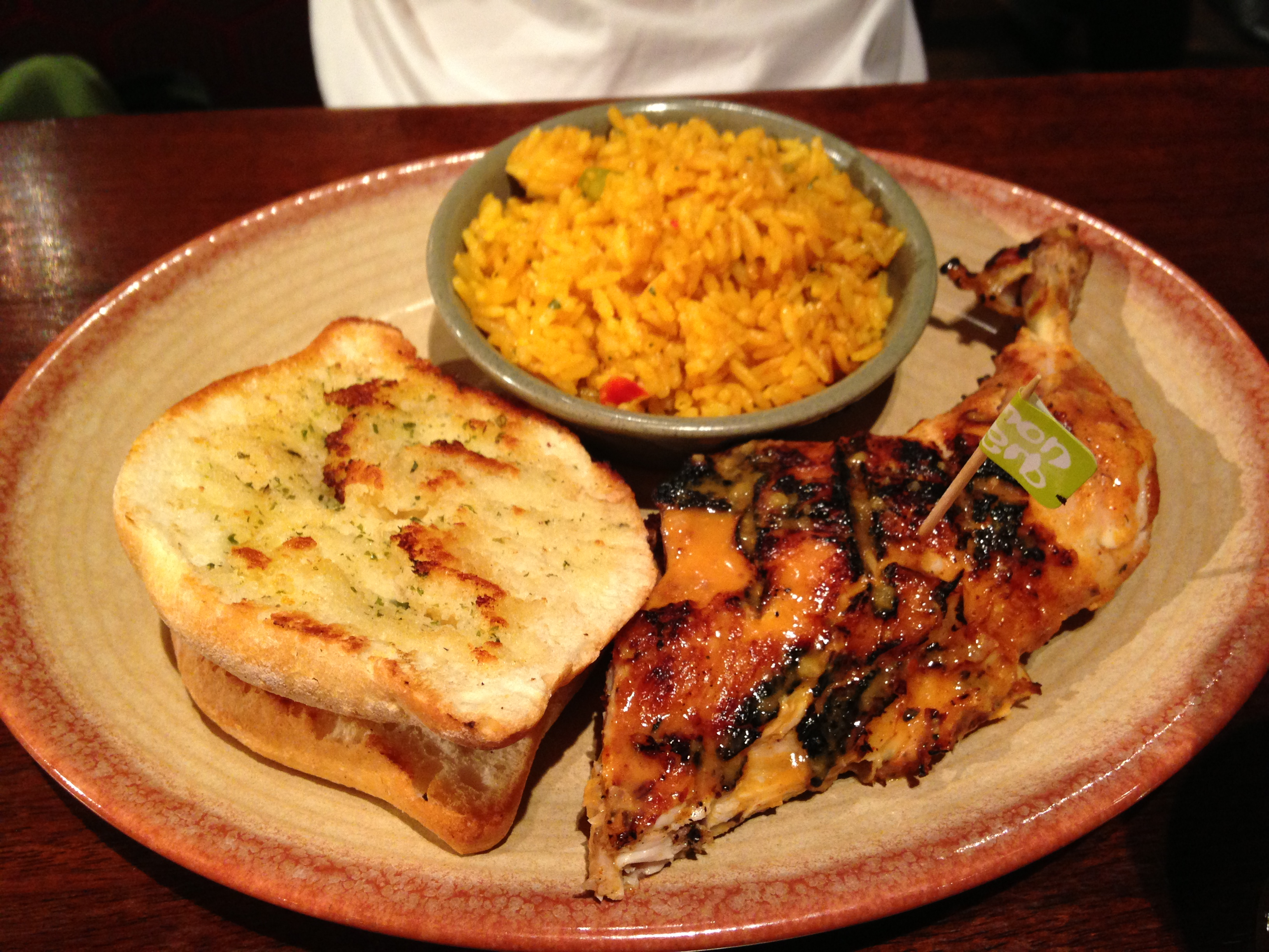 nando's grilled chicken dark meat with sides of rice and garlic bread
