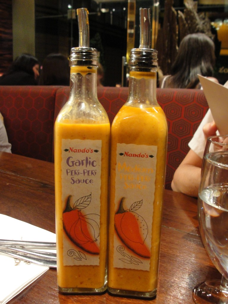 nando's garlic peri-peri sauce and medium peri-peri sauce in glass jars with metal tops