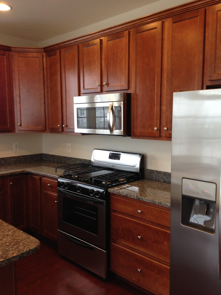 new kitchen in condo with stainless steel appliances, wood cabinets, and granite countertops