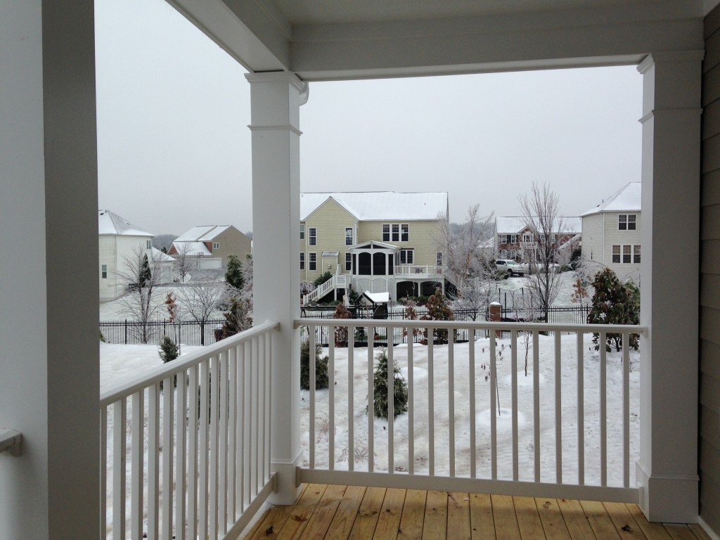 new condo porch with white railing and view of houses in back