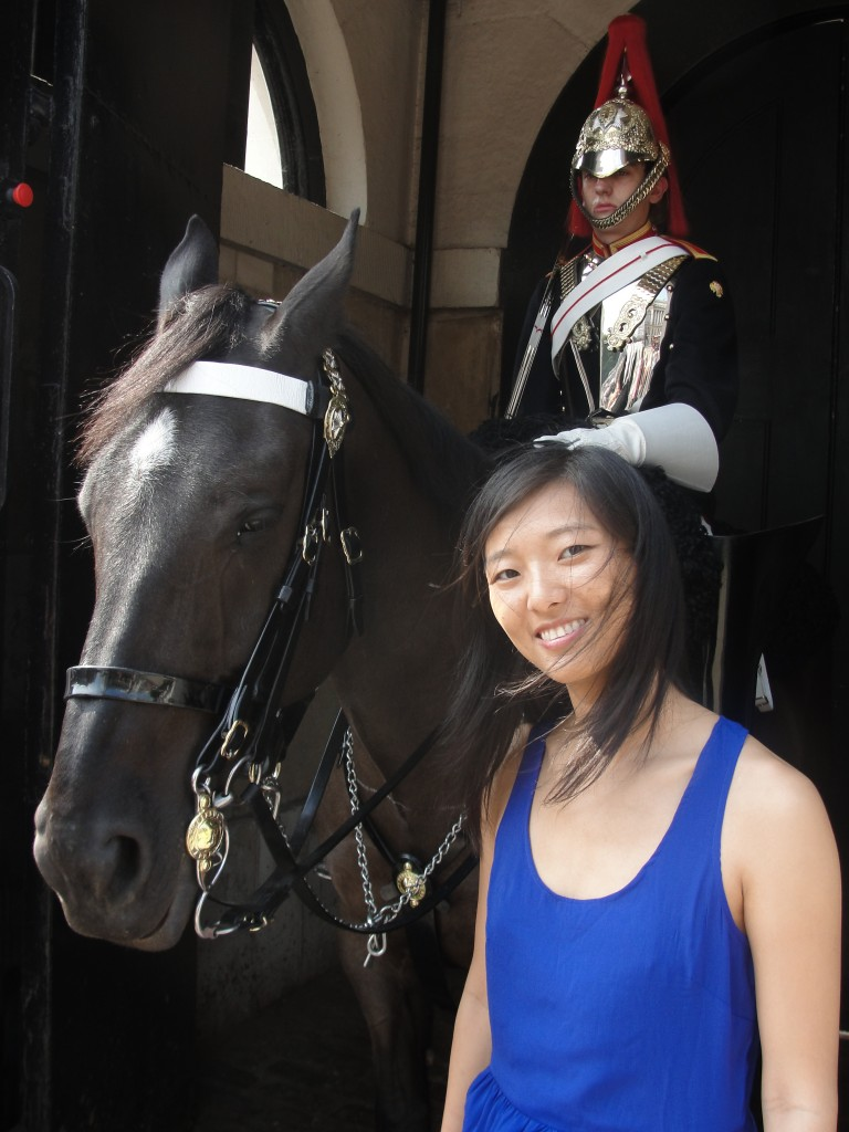 girl standing next to horse with guard sitting on it