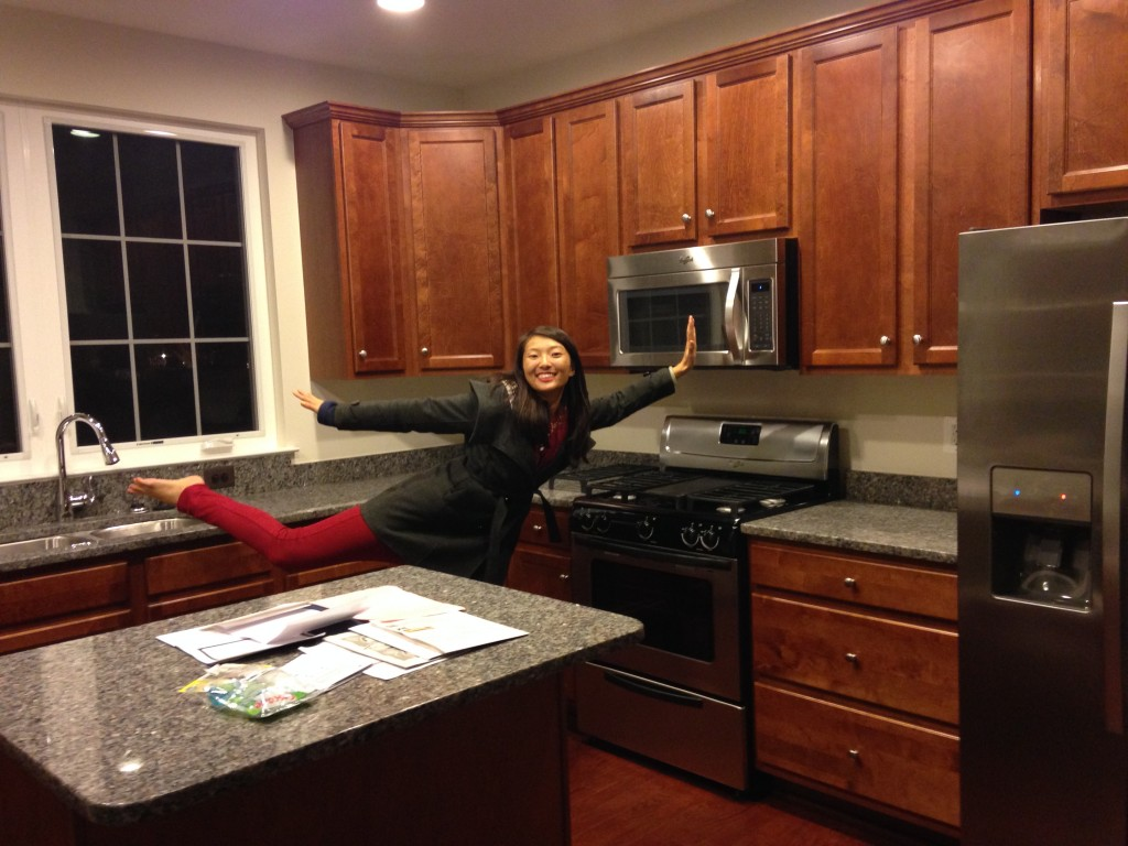 happy girl prancing in kitchen of brand new condo balancing on one leg with arms and other leg outstretched