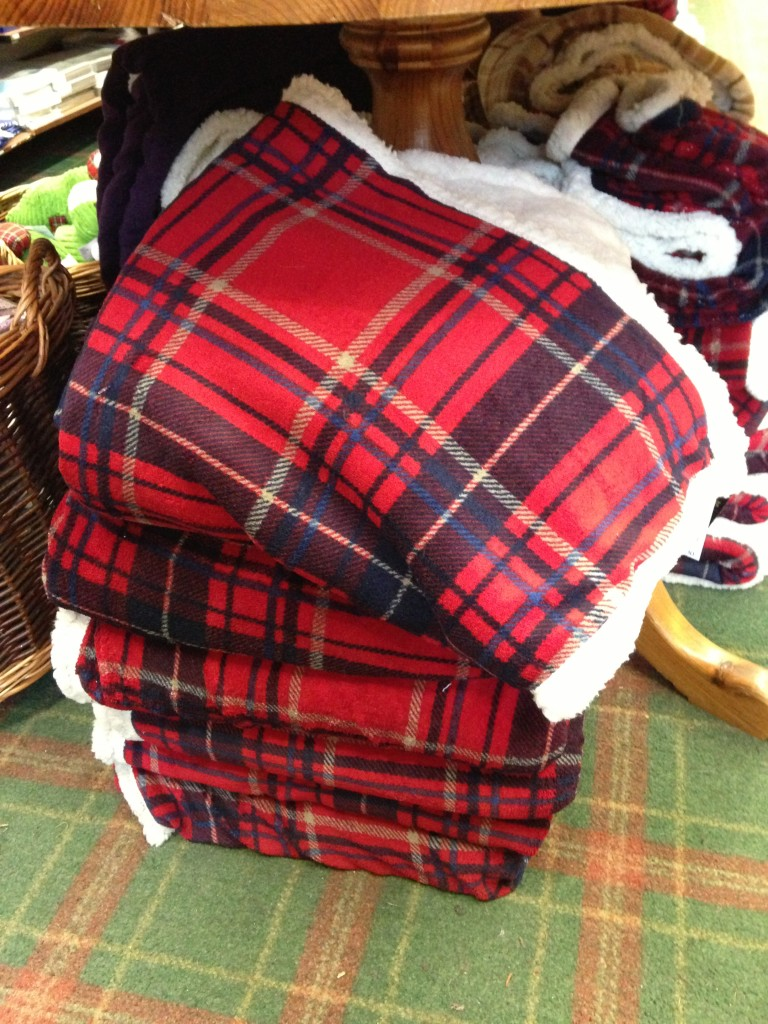 pile of red scottish print sherpa blankets