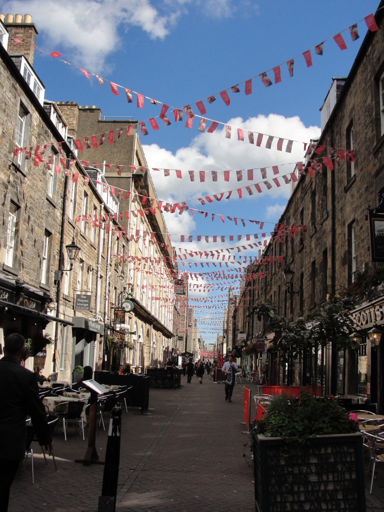 strings of small red flags stretching across rose street walkway