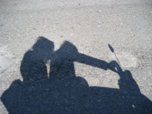 shadows of two people riding on moped