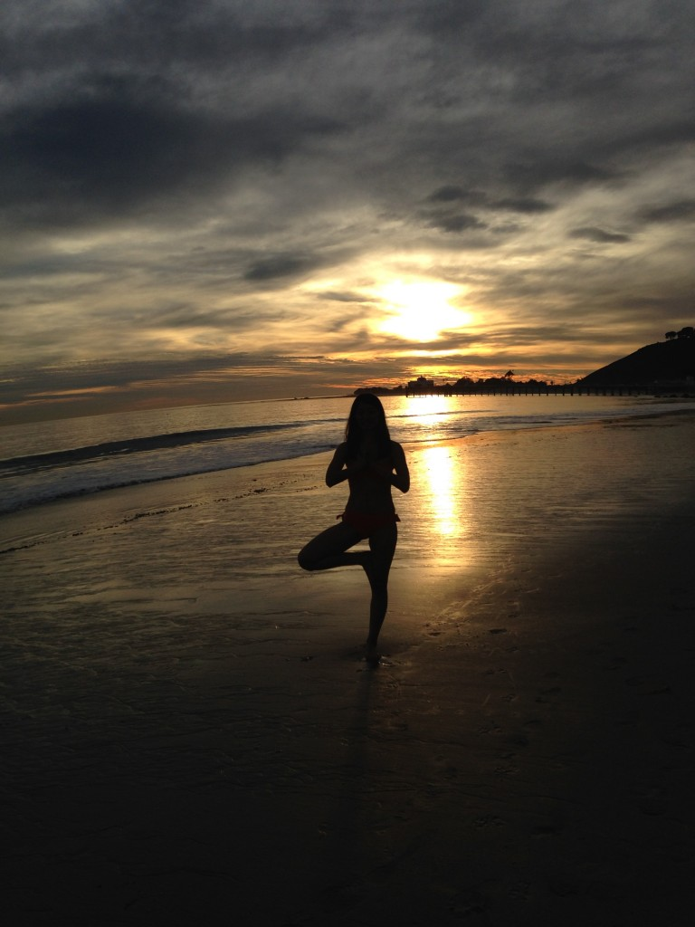 silhouette of girl doing yoga tree pose with backdrop of setting sun through clouds at beach