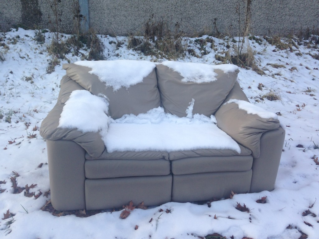 sofa sitting by side of road covered in snow from storm