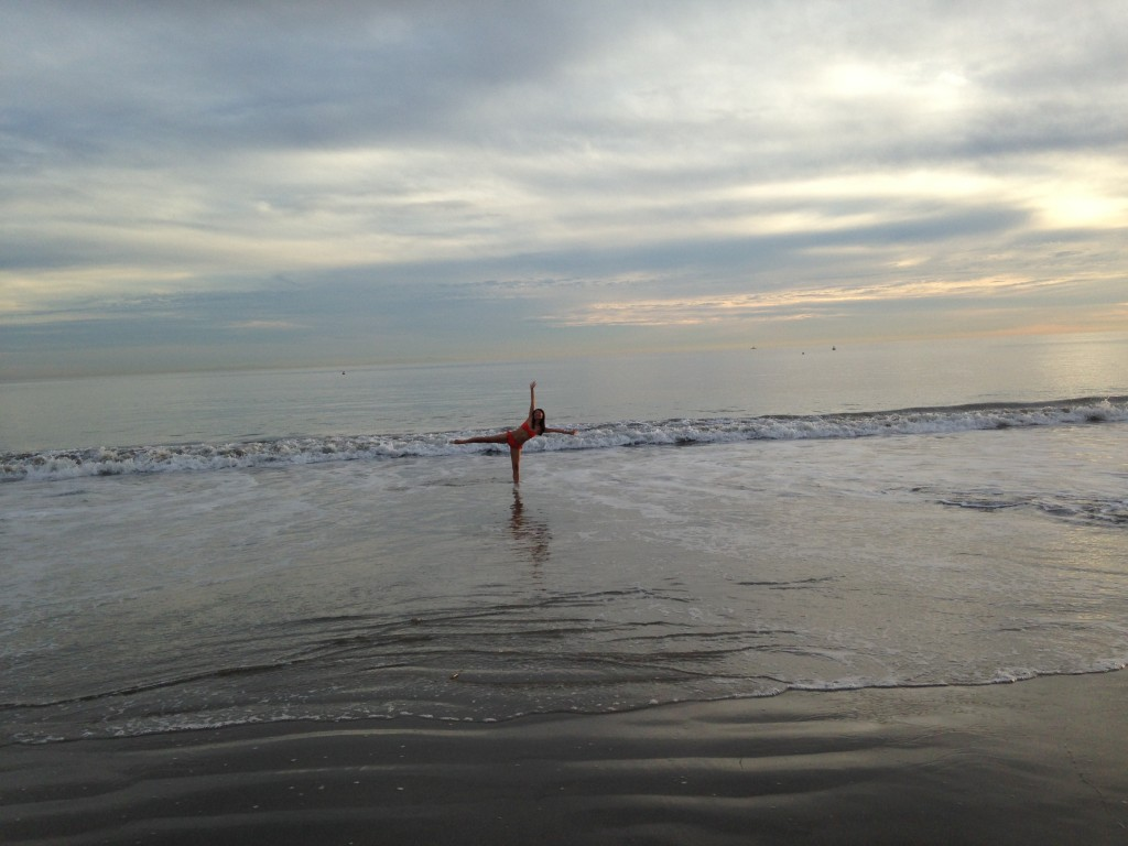 girl standing in ocean at beach stretching arms and legs out like starfish