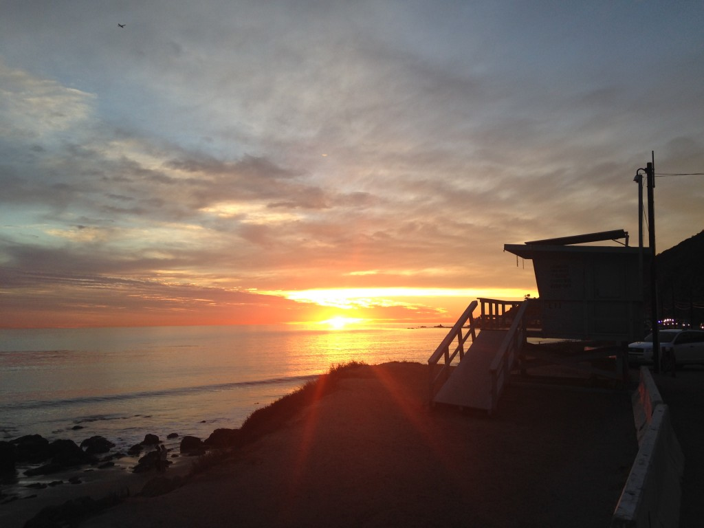 view of sunset from side of road by beach with lifeguard station silhouette