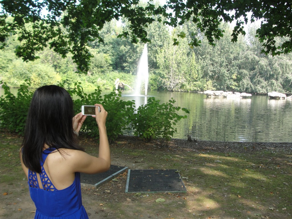 girl using iphone to take picture of lake