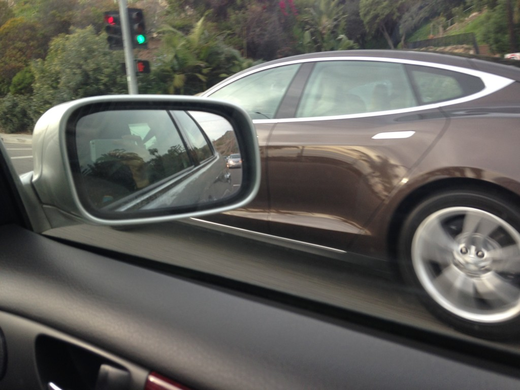 tesla model s driving by on pch in malibu