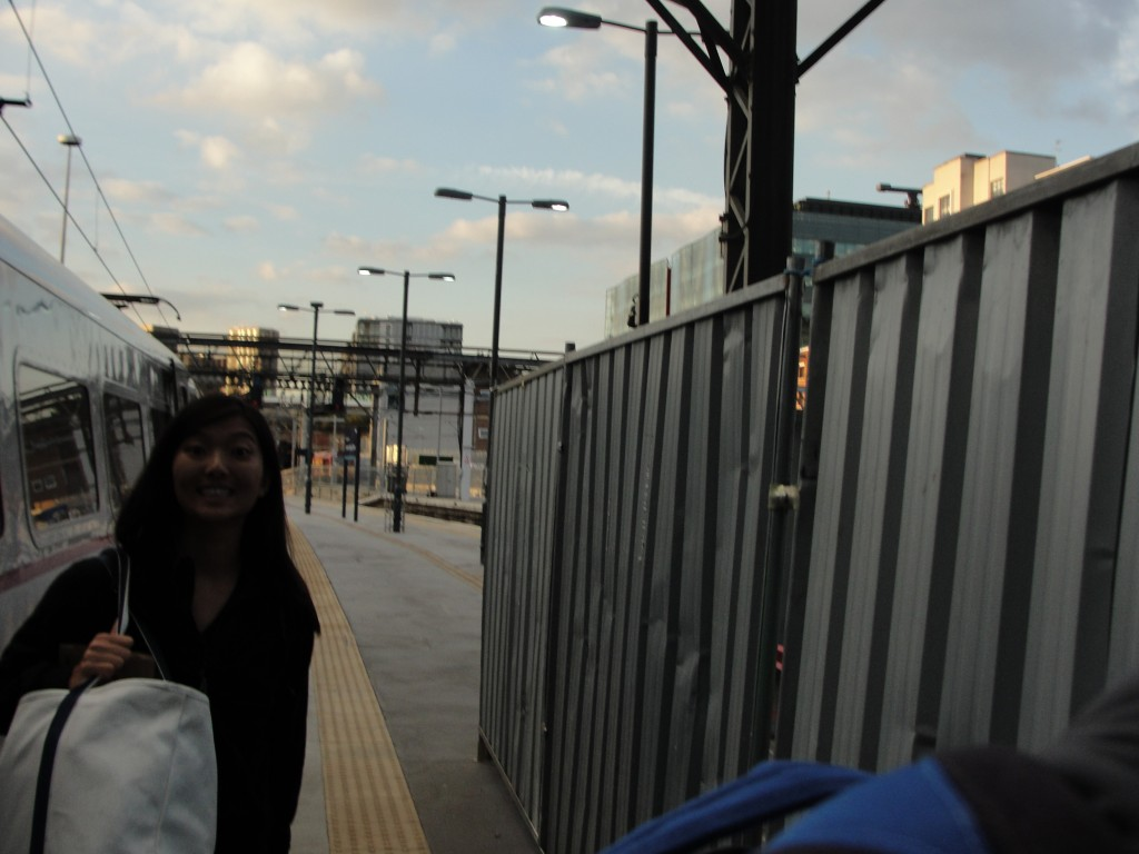 girl grinning with bag near end of train station platform
