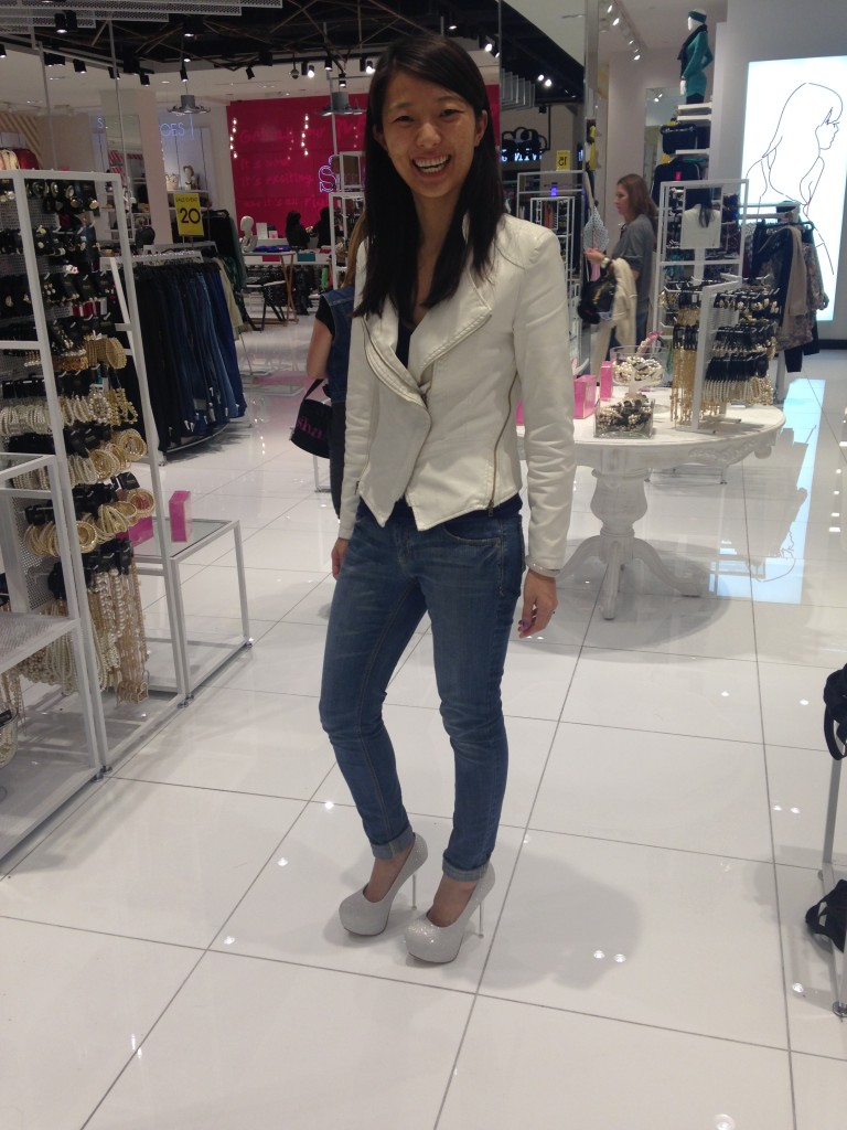 girl laughing trying on white glittery platform heels in store