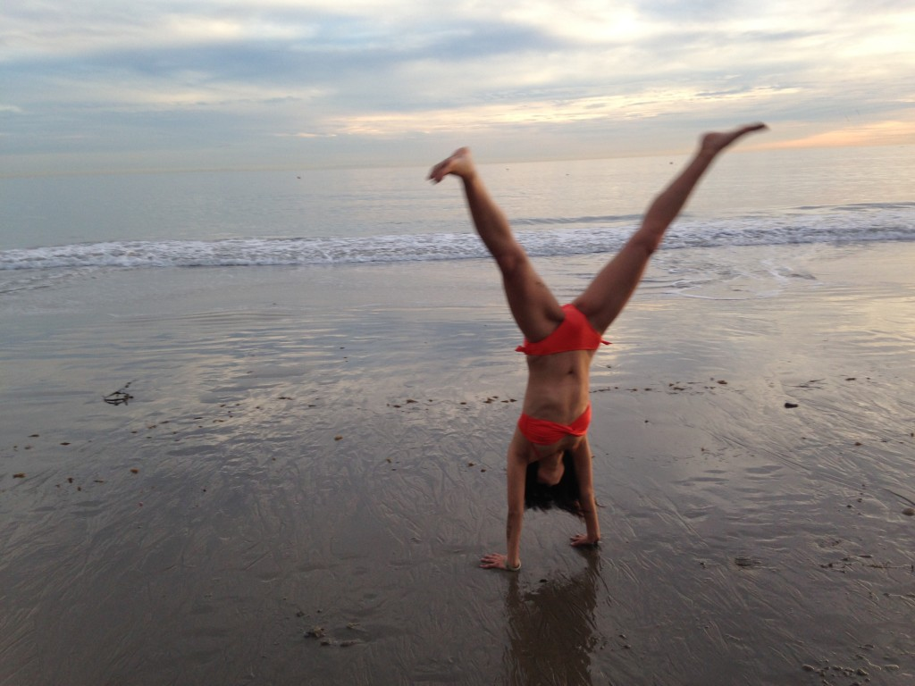 girl in orange bikini doing cartwheel at beach paused in handstand