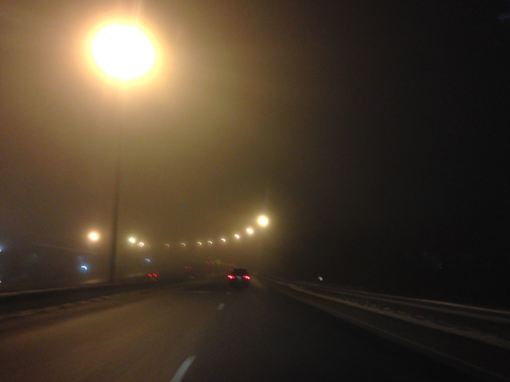 very foggy night with street lights glowing yellow and blurry on the road
