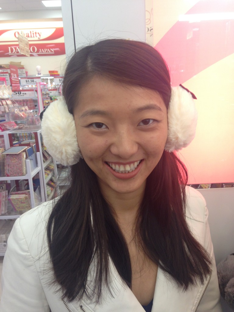girl wearing white fuzzy earmuffs in store