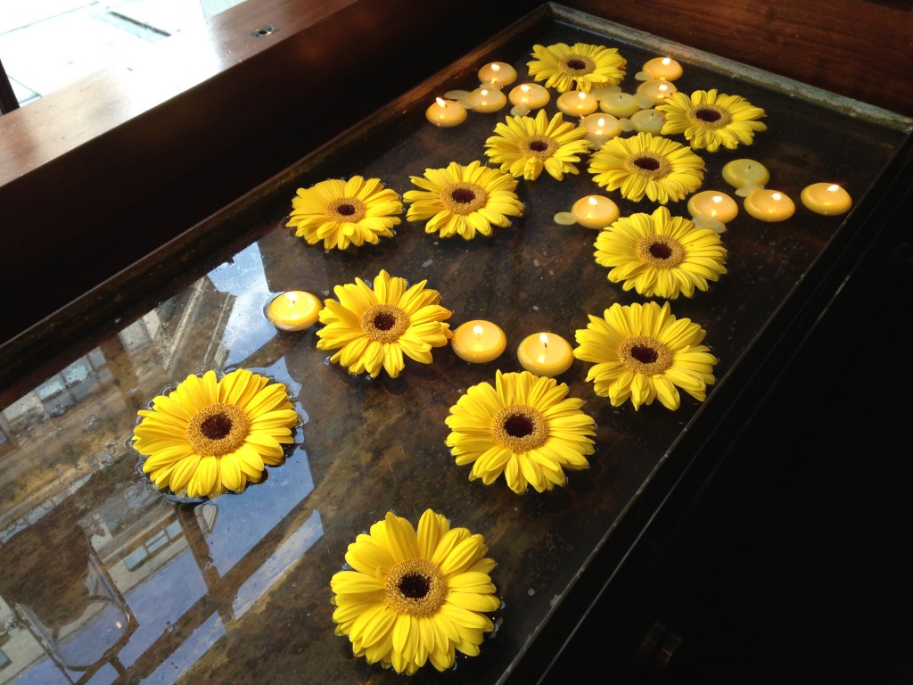 yellow flowers and floating candles on water