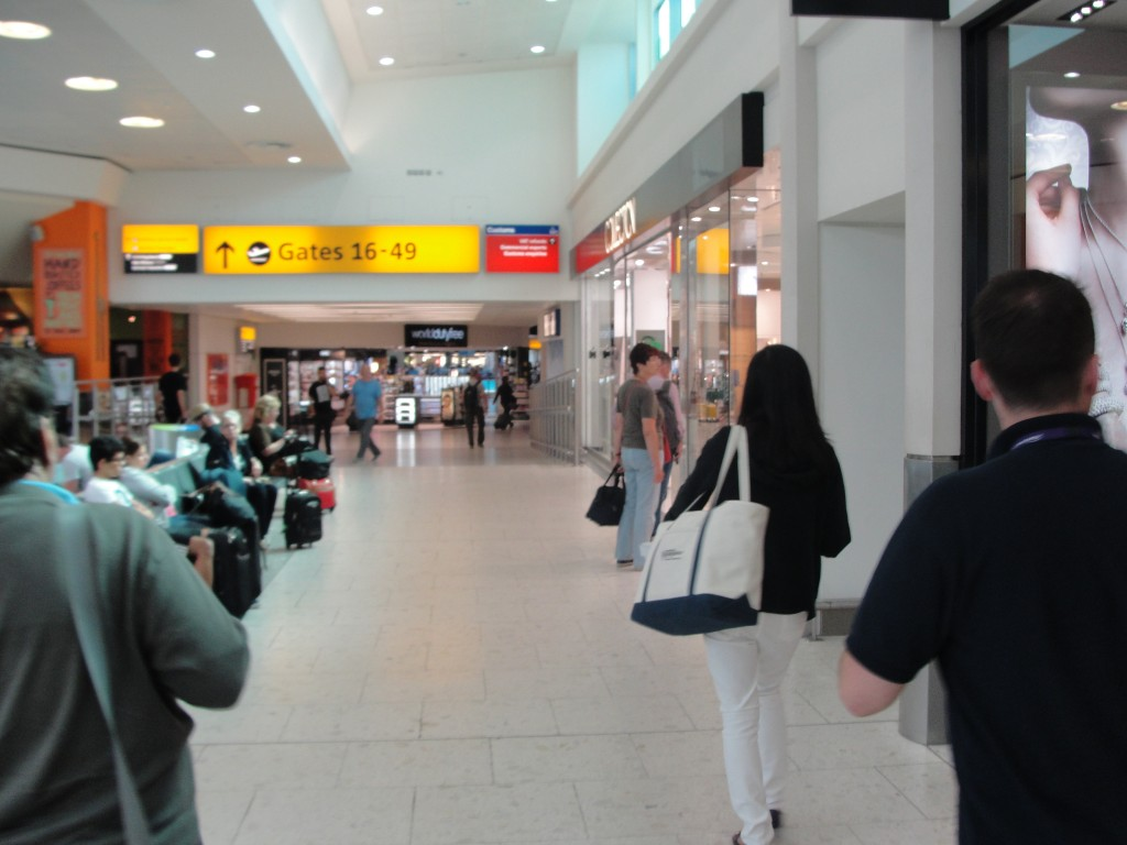 walking in airport hallway lined with stores towards departure gates