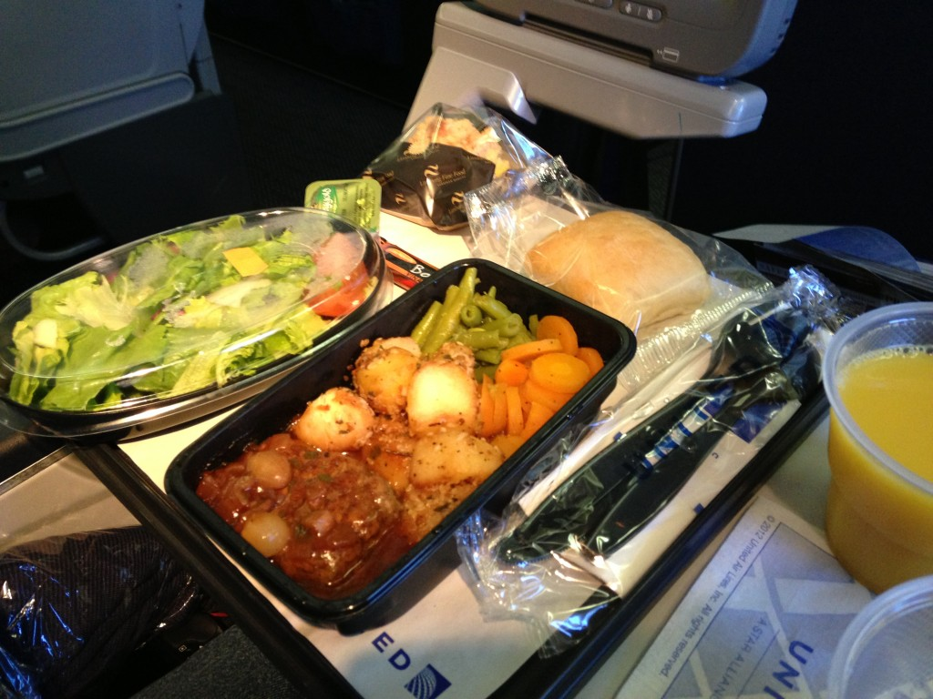 airplane meal with salad, beef and vegetables, bread, and orange juice