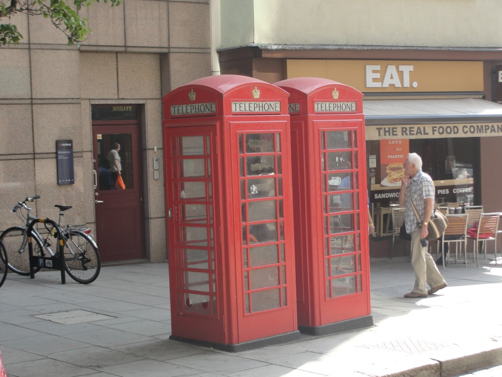 two red british telephone booths on streets of london
