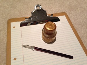 bottle of gold calligraphy ink and glass pen on clipboard with lined paper