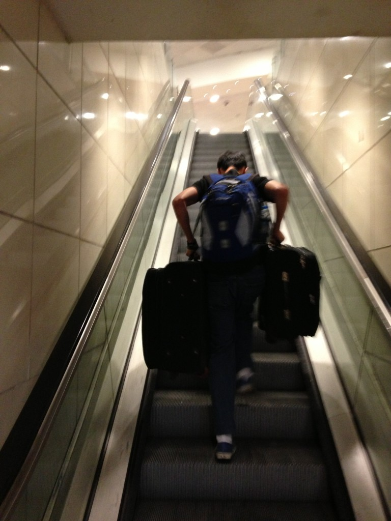 guy carrying two suitcases one in each hand up out of order escalator