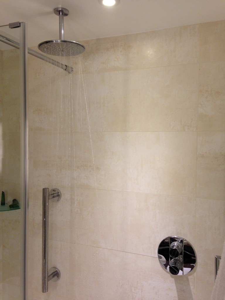 large showerhead extending from ceiling raining down water