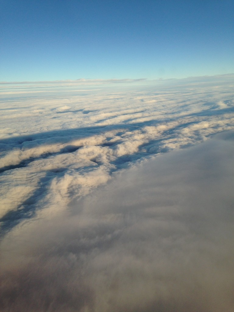 overhead view of gray clouds and white clouds with shadows of setting sun