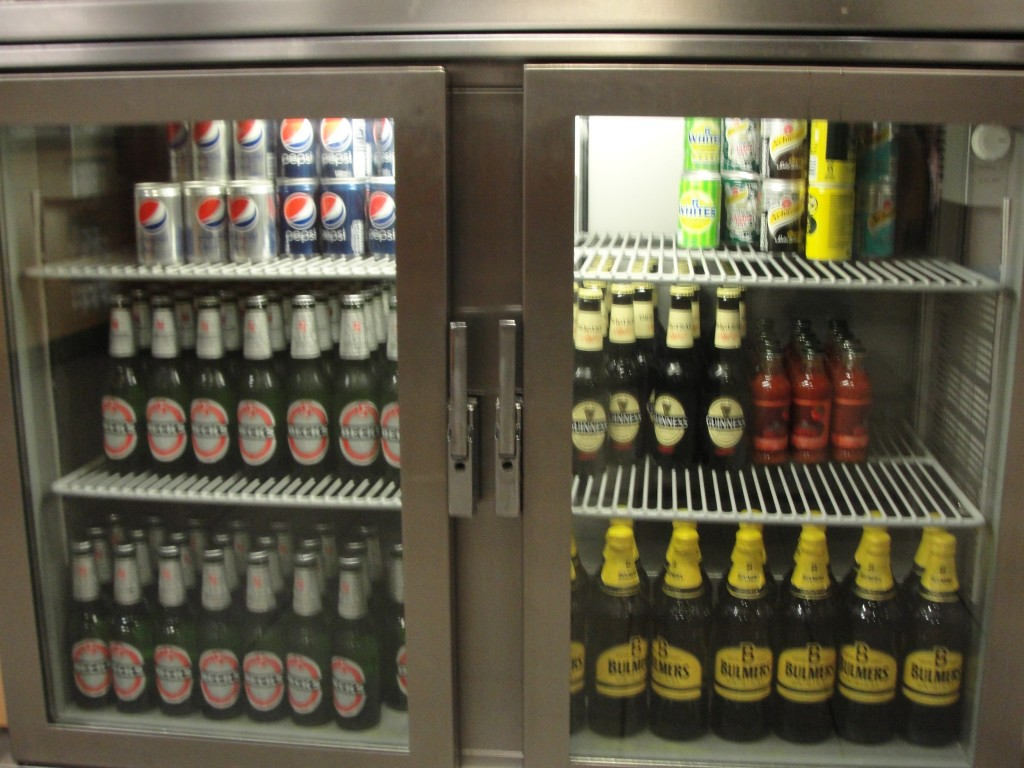fridge with glass doors showing sodas and beers inside