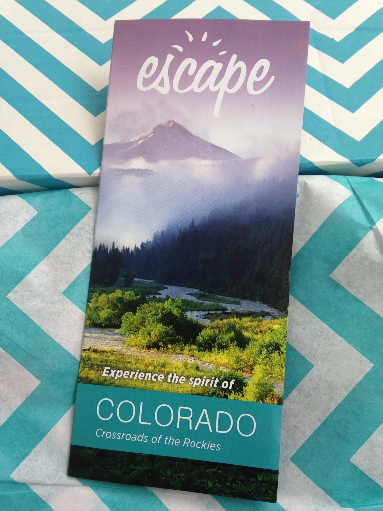 escape monthly january colorado box info card against blue and white chevron background