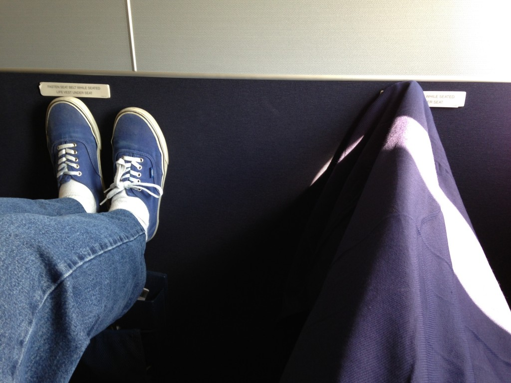 two pairs of feet propped up on wall in airport