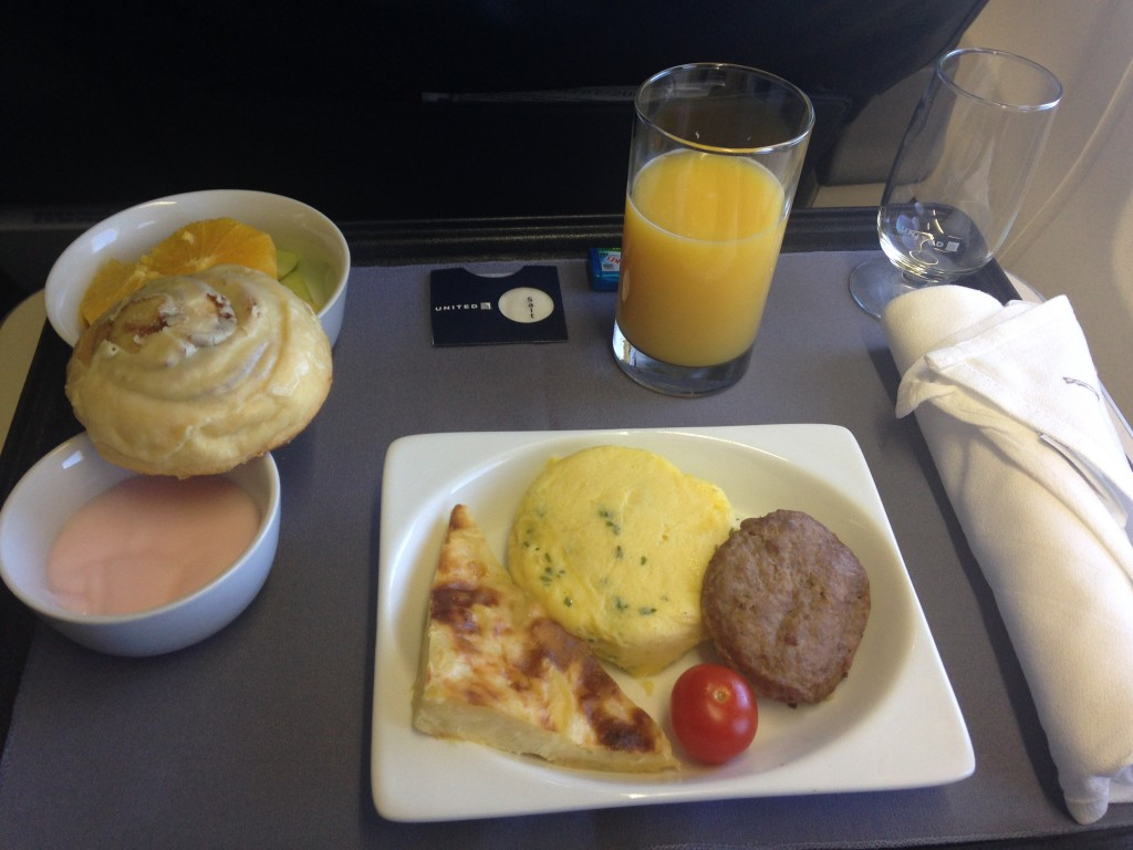 breakfast meal served in first class on united flight, with eggs, potatoes au gratin, meat patty, tomato, cinnamon roll, fresh fruit, and orange juice