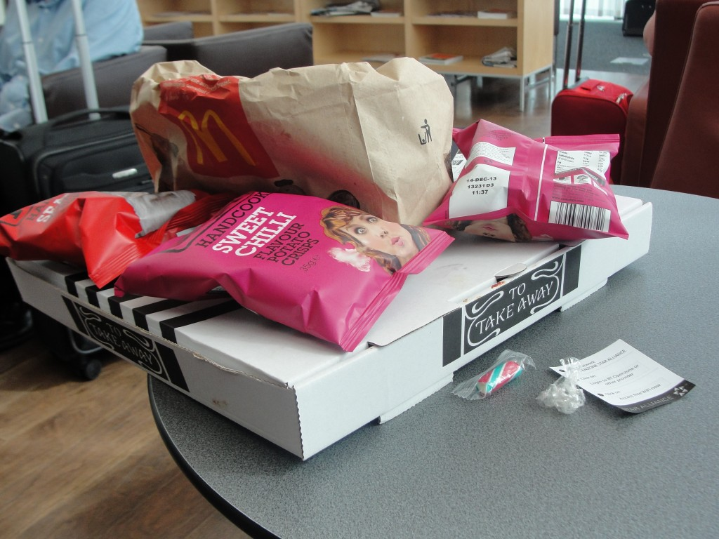 pile of pizza box, bags of chips, and mcdonald's bag