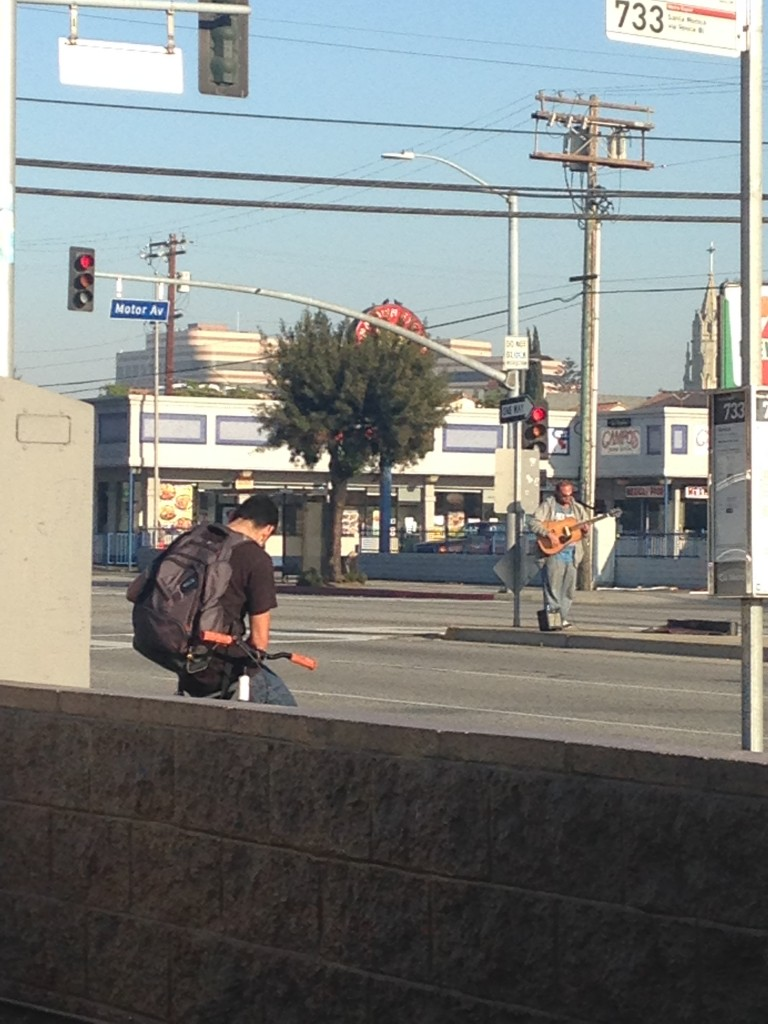electric guitarist playing music in middle of road at intersection in culver city