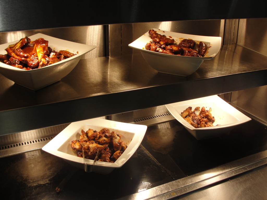 bowls of chicken wings and pork ribs under heat lamps