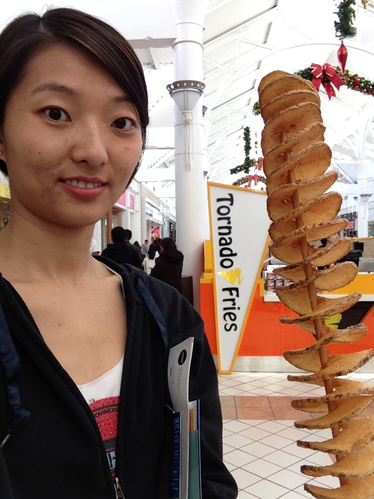 girl holding giant stick of tornado fries in front of kiosk in mall