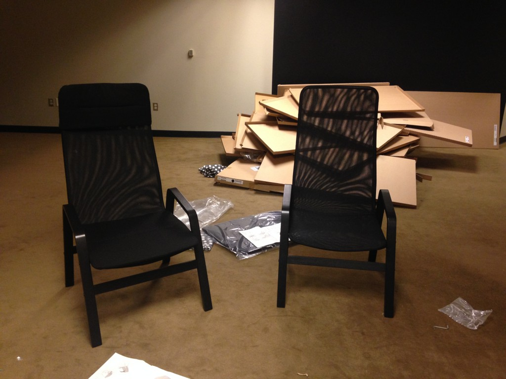 two mesh ikea lawn style chairs freshly built with cardboard boxes in background