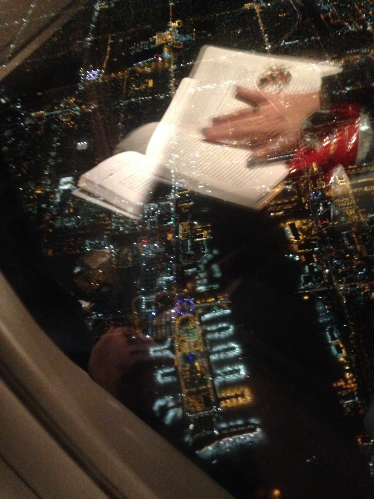 view of lax airport at night from airplane window with reflection of book and person's hand