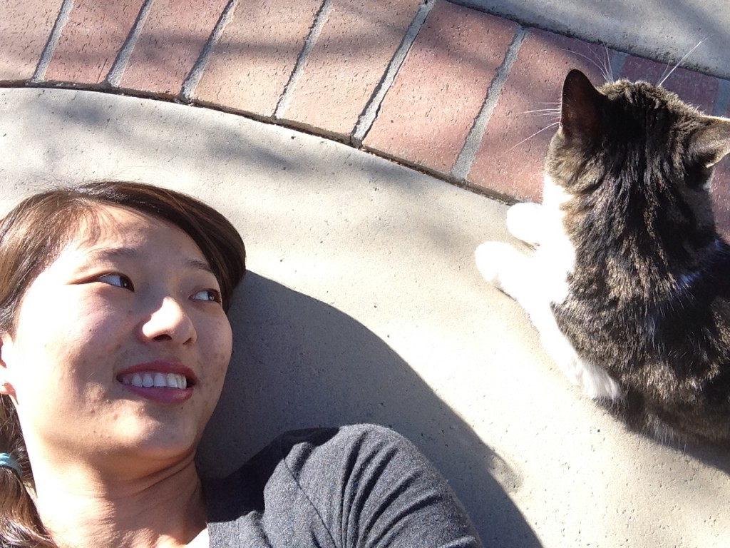 girl laying on ground looking over and smiling at cat looking into distance
