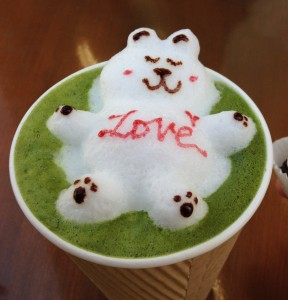 green tea latte drink with 3d latte art bear and the world love written on its belly