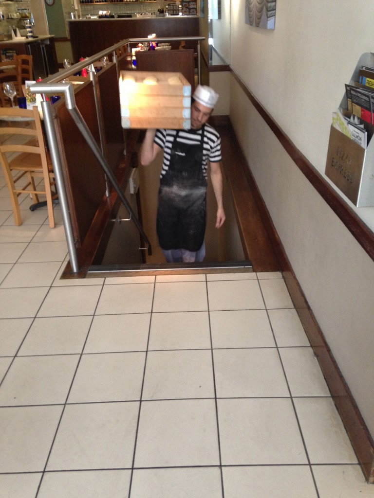 guy walking up stairs holding trays of dough for pizza express pizzas