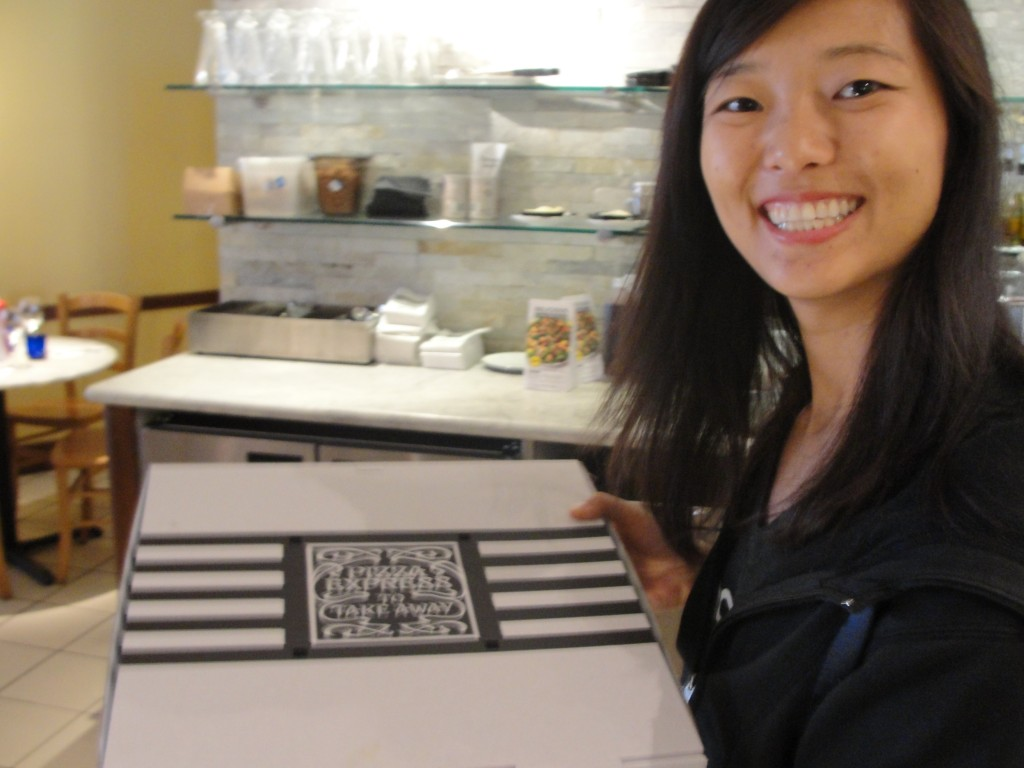 girl happily holding pizza express takeout box