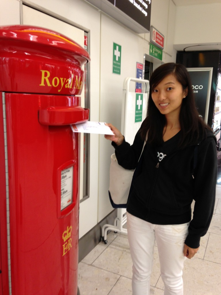 sending off mail in large red royal mail box