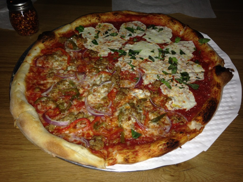 thin crust pizza with half sausage with red onions and half mozzarella with basil